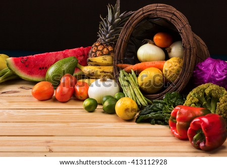 basket and table full of colorful fruits and vegetables that were purchased on the market, dark background - stock photo