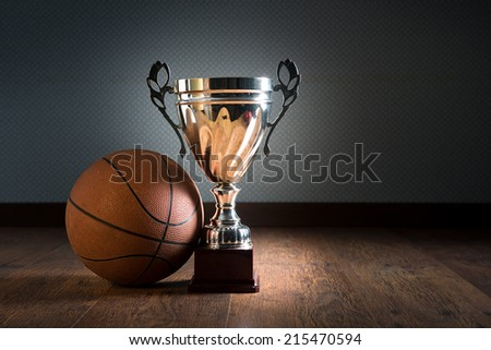Basket ball and gold bright trophy on hardwood floor. - stock photo
