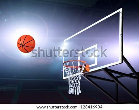 Basket ball heading the hoop with spotlights - stock photo