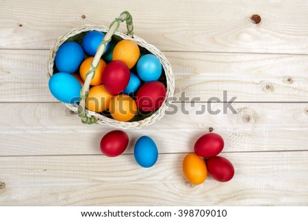 Basket full of hand-painted Easter eggs standing on a wooden surface.