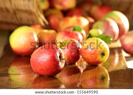 Basket of apples on a wet table - stock photo
