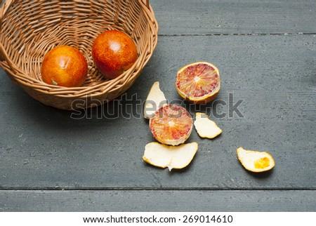 basket of blood oranges on wood black table - stock photo