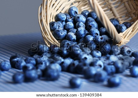 Basket of blueberries spilling onto blue tablecloth - stock photo