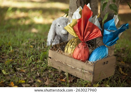 Basket of brazilian Easters eggs under a tree, with a bunny in the background. - stock photo