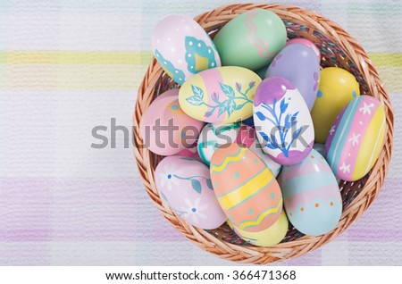 Basket of colorful Easter eggs on a pastel colored surface