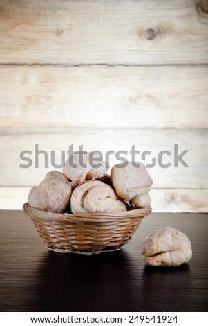 Basket of cookie on a black table against old wooden background.