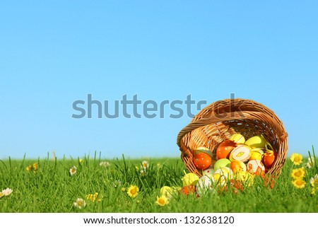 Basket of easter eggs on green grass at sunny day. - stock photo