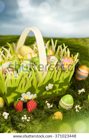 Basket of easter eggs on meadow. - stock photo