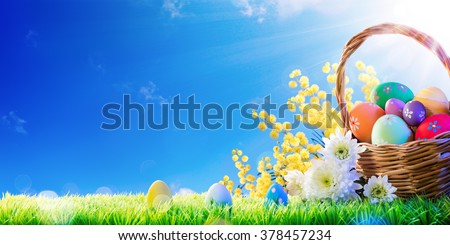 Basket Of Eggs Hand-Painted With Mimosa On Grass - Easter Holiday Background  - stock photo