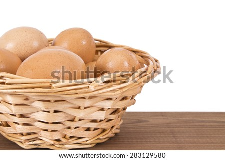 basket of eggs on the wooden table - stock photo