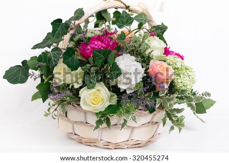 basket of flowers - roses peonies hydrangea on white background