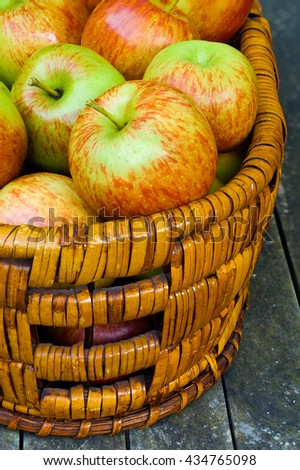 Basket of fresh apples on a rustic wood table. Concepts: Farm to table, healthy eating, local, abundance - stock photo