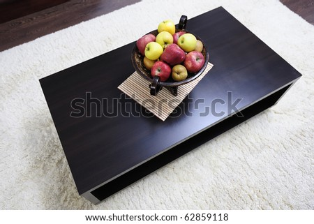 Basket of fresh fruits on a coffee table in a modern living-room - stock photo