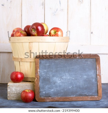 Basket of fresh picked apples with a slate for custom copy. - stock photo