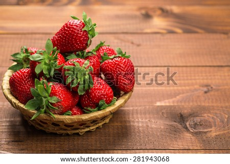 Basket of fresh strawberries on wooden board - stock photo