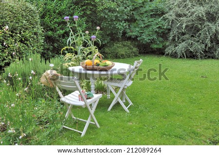 basket of fresh vegetables on a table  in a country garden - stock photo