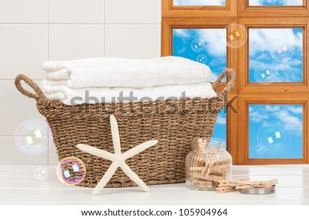 Basket of freshly laundered towels with pegs and bubbles - stock photo
