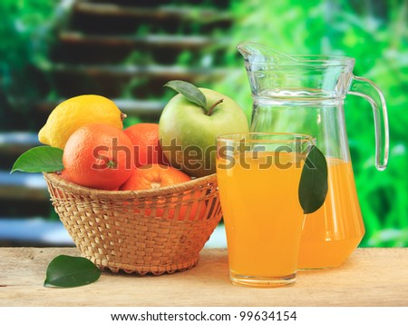 basket of fruit and juice on a wooden table in the garden