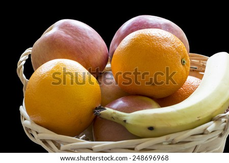 Basket of fruits on black background, containing oranges, apples and bananas - stock photo
