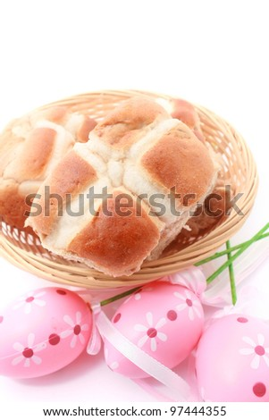 Basket of Hot Cross Buns and Easter Eggs isolated on white