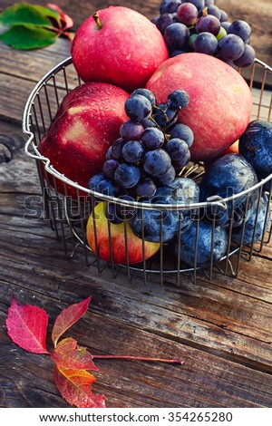 Basket of metal rods with ripe apples and grapes - stock photo