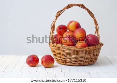 basket of nectarines  on white wooden table