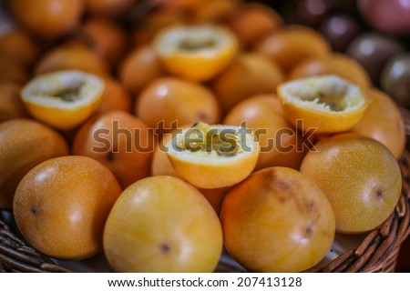 Basket of orange colored Passion fruit at a local farmer's market. There two fruits cut into four halves, showing their juicy inside. - stock photo