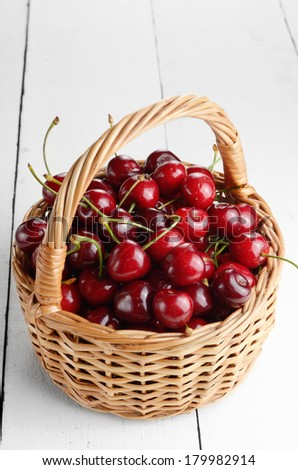 Basket of organic Cherries on white table