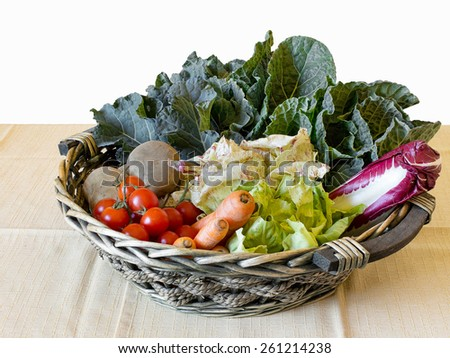 Basket of organic vegetables in basket on table. Part isolated on white background .Includes potatoes, tomatoes, chicory, cabbage and carrots. - stock photo