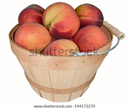 Basket of Peaches:  A small wooden basket holds large ripe peaches.  - stock photo