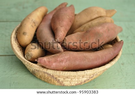 Basket of red yams and sweet potatoes on green table - stock photo