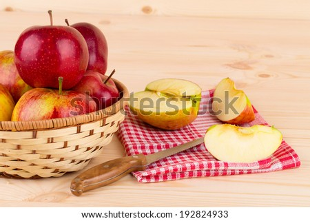 Basket of ripe apples with knife and sliced apple located on wooden table