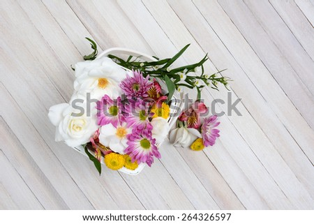 Basket of Spring flowers on a wood table. Overhead shot in horizontal format with copy space.