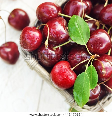 Basket of sweet  fresh cherries on wooden background, selective focus