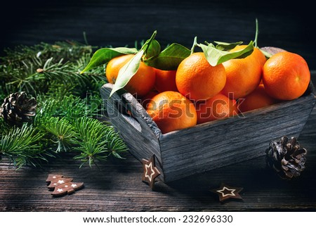 Basket of tangerines with leaves on wooden table with Christmas decor and Christmas tree. - stock photo