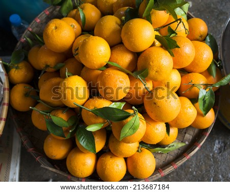 Basket of tropical oranges in market - stock photo