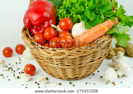 Basket of Various Vegetables with Pepper, Carrots, Lettuce, Onions, Garlic, Parsley, Tomatoes, Broccoli and Edible Mushrooms on the white wooden table