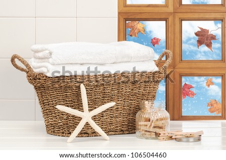 Basket of washing with raindrops on window and falling autumn leaves - stock photo