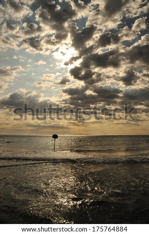 Basket on the shoreline with dramatic sky - stock photo