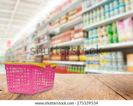Basket on wood floor and Supermarket blur background ,Product shelf sauce - stock photo