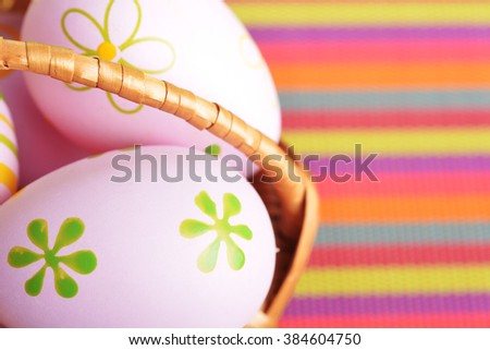 basket wicker with decoration easter eggs on striped napkin  - stock photo