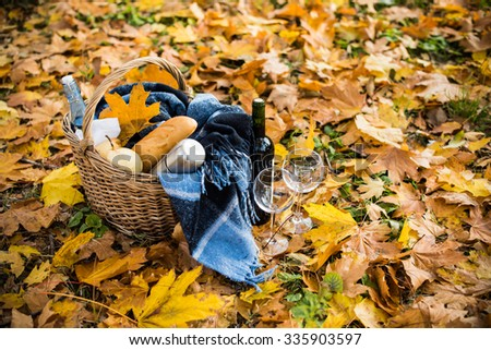 Basket with a blanket, coffee, food, wine and glasses on yellow autumn leaves. A cozy autumn picnic in the park, a warm autumn day.