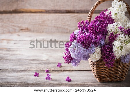 basket with a branch of lilac flower on a wooden background - stock photo
