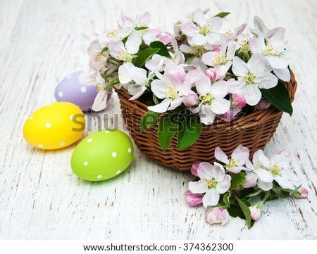 Basket with apple blossom and easter eggs on a wooden background