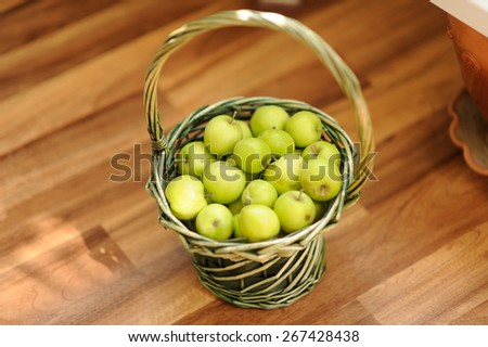 basket with apples on the wooden floor - stock photo