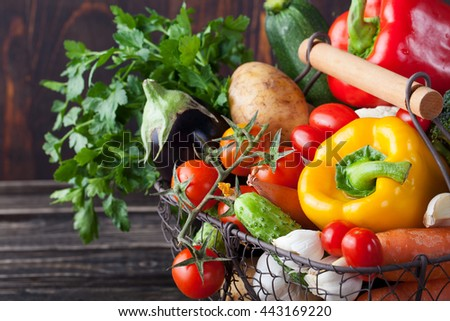 Basket with assortment of fresh vegetables on a wooden rustic background - stock photo