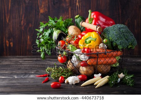 Basket with assortment of fresh vegetables on a wooden rustic background Copy space - stock photo
