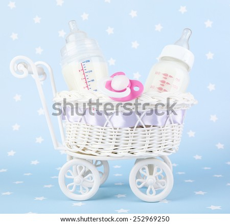 Basket with baby milk bottle and pacifier on blue background - stock photo