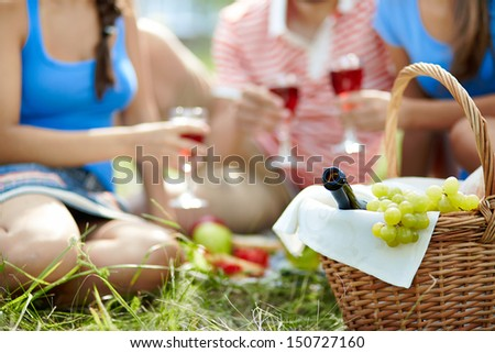 Basket with bottle and grapes on background of cheering friends - stock photo