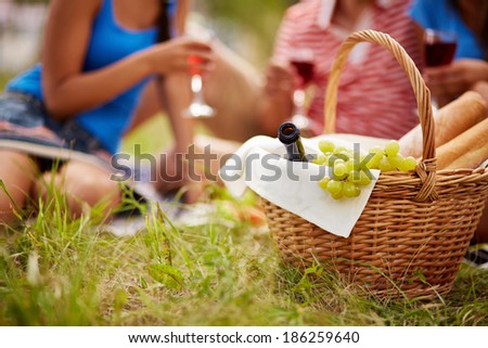 Basket with bottle, bread and grapes on background of cheering friends - stock photo